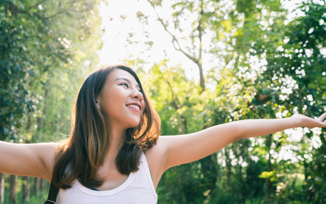 Female hiker spreading her arms out to enjoy the sunlight